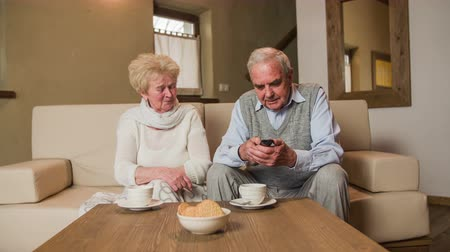took : Grandmother give TV remote to elderly husband . Senior couple sit on sofa and trying to watch television in living room. Woman gives remote to husband but it doesnt work. Stock Footage