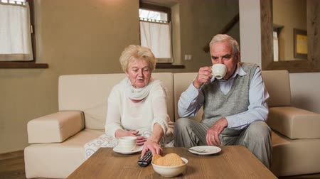 took : Elderly woman explaining husband about TV remote . Lovey senior couple sit on beige sofa together and watch television with cups of tea on table in front. Grandma explaining husband about ownership of TV remote.