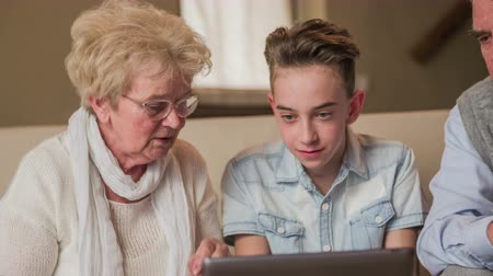 partially : Old woman questioning boy about computer . Grandmother and grandson watching on laptop screen and having a conversation. Elderly woman using eyesight glasses.