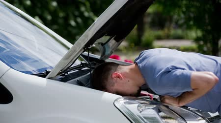 çabaları : Man put head under car bonnet looking behind headlights. Man in blue shirt checking how to remove headlights, put head inside to see better. Home repair of car. Sunny day.