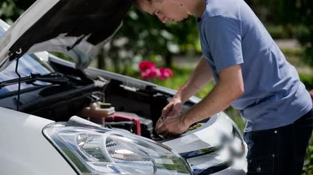 compares : Man replacing car bulb headlights. Young mechanic put out old broken bulb from car headlight and putting new one leaning inside under car bonnet.