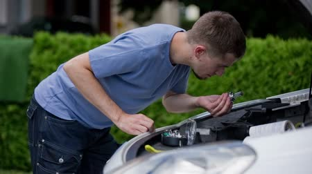 compares : Man put out bulb from car headlight and look at it. Young male mechanic in blue shirt fixing car headlights, checking if bulb is broken. Stock Footage