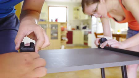 two wheeled : Two person screwing wheels on table jib shot . Boy and girl putting together a table with wheels, screwing on bottom of new computer desk. Shoot in bright living room with kitchen in background.
