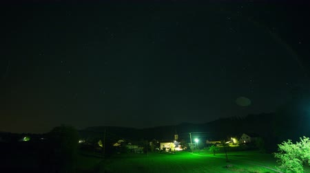 perseids : Village at night time lapse . Lights shining, airplanes and comets flying over the sky, fog rising. Fast motion.