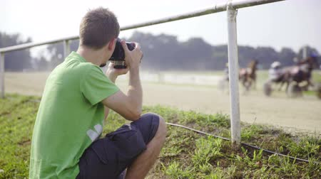 sulky : Photographer shooting hippodrome racers . Official photographer with professional camera making photos of harness racing winners. Kneeling beside the fence.