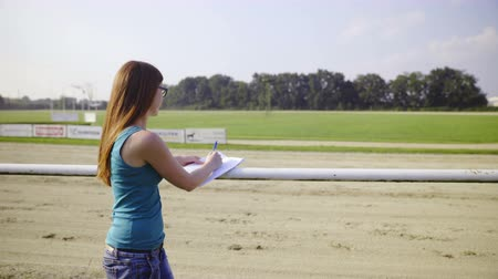 Woman with bulletin on hippodrome. Young female person viewing harness race and carefully monitoring bulletin with competitors data.