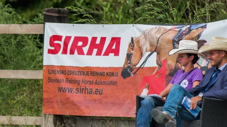 assess : Judges at SIRHA reining competition. Two western judges sit on chair and observe competitors at SIRHA competition. Big sign in background. Stock Footage