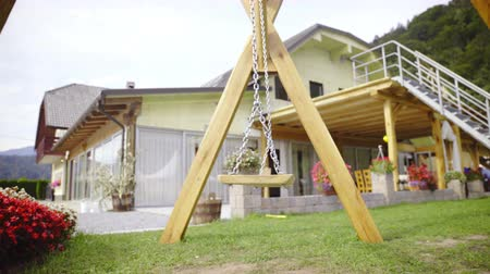 Empty wooden swing in front of house 4K. Sliding under swing moving without anyone sit on it. Green lawn around.