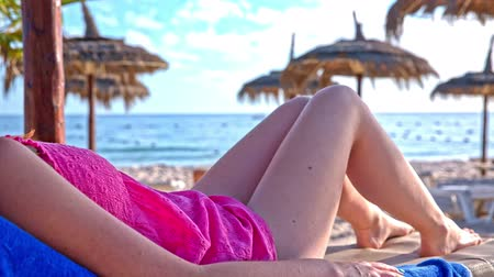 banhos de sol : Person lying on lounger at the beach. Female person in light pink dress laying on lounger and hiding under straw umbrella. Blue sea in background. Vídeos