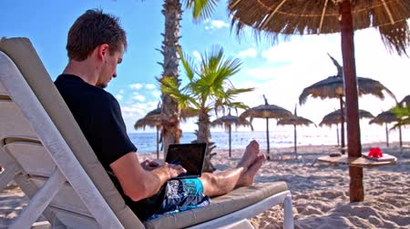 jovem : Man working on laptop on the beach. Male person sit on lounger with small laptop PC on legs typing. Beautiful sand beach and sea in background. Under straw umbrella.