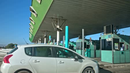 плата : Driving through toll station in Tunisia. Side shot from vehicle while driving on to green toll station, other vehicles beside in lines.