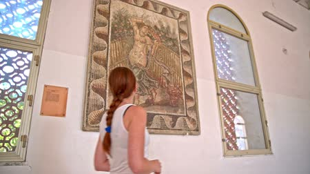 Famous Venus mosaic found in Carthage ruins. Female person walking by a mosaic picture on wall with Venus, god of love.