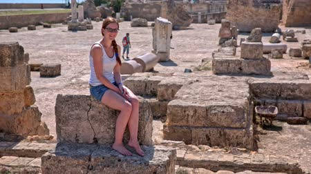 Female tourist posing on ruins of Carthage spa. Attractive young woman sit on a big rock with ruins of Carthage in background. Bright sunny day.
