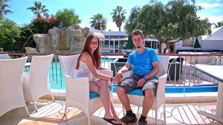 Couple sit at cafe with pool in background. Young man and woman posing at pool cafe alone. Man in blue shirt, both smiling. Attractive couple on vacation.