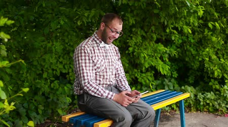 pólos : Smiling man in glasses sitting on a bench and surfing in touch p Stock Footage