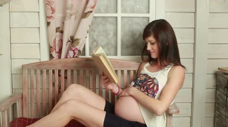 sitting room : Future mother reading and stroking tummy