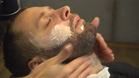 kadeřník : Barberman using soft cream on face of man with beard