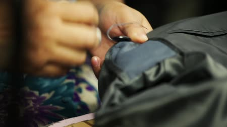 vyšívání : Sewing a button onto a bespoke tailored suit