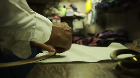 medir : Bespoke tailor working at a factory, making chalk lines and cutting fabric for a suit