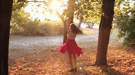 éteri : romantic cheerful girl spinning in the Park in the red dress
