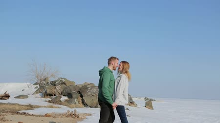 blízkost : young man and woman walk together along the beach in the spring.