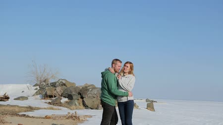 близость : young man and woman walk together along the beach in the spring.