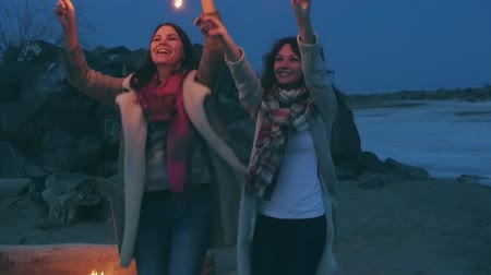 jump away : young women with sparklers against the night shore
