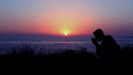 repenting : Man Praying by the Sea at Sunset Stock Footage