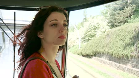 kıvırcık saçlar : Young Female Passenger Inside the Train Looking Out the Window on the Road. Portrait of Sensual Brunette Woman with Curly Hair and Red Shirt in the Wagon.
