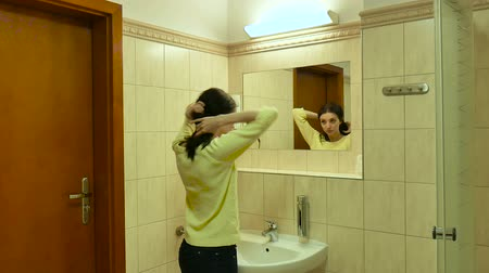 lavatório : Rear View of Young Active Woman near the Mirror. Attractive Girl Opens the Wooden Door and Enters to the Bathroom. Brunette Looks at Herself with Smile and Pleasure.