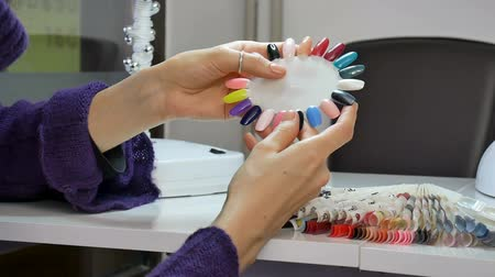 указывать : Female Client of Beauty Salon with Well-groomed Hands Choosing Color on Nail Palette.