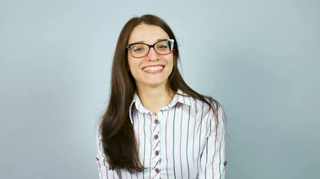 model : Laughing Happy Smart Female Student Wearing Optical Eyeglasses Posing in Studio on Grey Background. Stock Footage