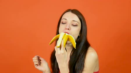 banan : Young Healthy Woman with Perfect Skin Eating Banana on Bright Orange Background. Tropical Fruits. Vegetarian Eating Concept Wideo
