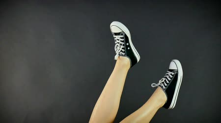 oneperson : Female legs in classic black and white sneakers. Legs are raised upwards and dangle from side to side. Gray, black background. Classic shoes, retro style. Healthy lifestyle Stock Footage