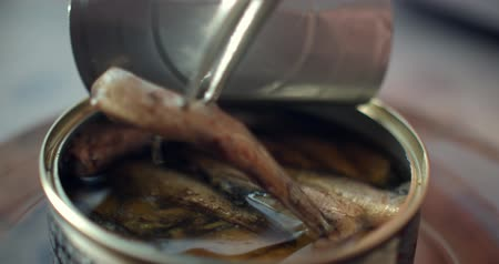 sprats : Using fork takes a smoked sardines from a tin can