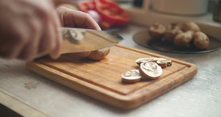 терпение : Man hand carefully cut wild mushrooms on a kitchen wooden board Стоковые видеозаписи