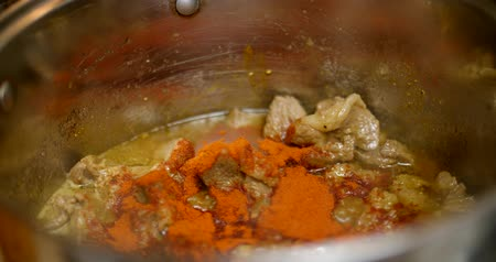 garnishing : Putting hot pepper in the boiling meat in a saucepan
