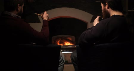 pálinka : Two guys smoke near the fireplace and drink cognac vape against a classic smoking pipe