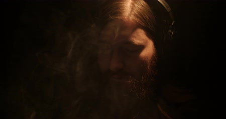 курильщик : A bearded man in the darkness smokes an electronic cigarette and listens to music