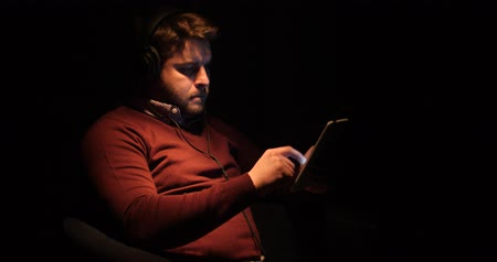 suite : A handsome man uses a tablet and listens music in a dark room