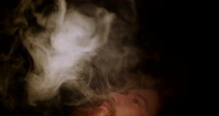 никотин : Bearded man in the dark exhales a thick smoke up
