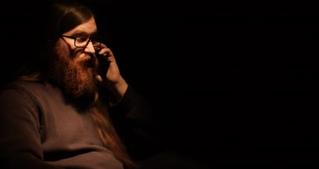 スイート : Bearded man talking on the phone in the darknes 動画素材