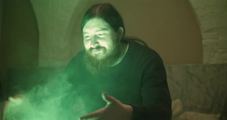 vaper : The bearded guy inhales the green smoke
