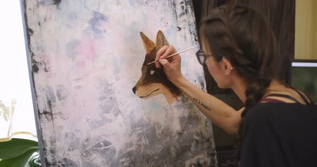 image house : Girl artist draws a fox, medium plan. Artist paints picture on canvas with acrylic paints in her workshop