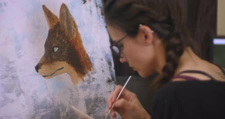 image house : Girl artist draws a fox, picture sliding. Artist paints picture on canvas with acrylic paints in her workshop