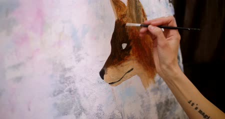 image house : Artist paints picture on canvas with acrylic paints in her workshop. Girl artist draws a picture, fox muzle, closeup