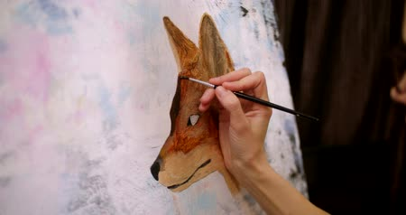 paleta : Artist paints picture on canvas with acrylic paints in her workshop. Girl artist draws a picture, fox muzle, closeup