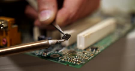 mikroişlemci : smoking soldering iron on a computer motherboard closeup Stok Video
