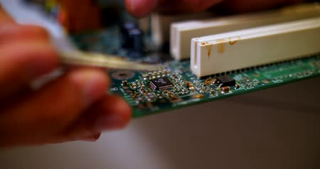 интегрированный : smoking soldering iron on a computer motherboard closeup Стоковые видеозаписи