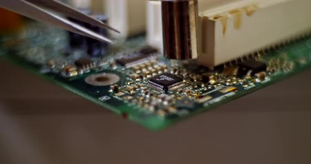 полупроводник : smoking soldering iron on a computer motherboard closeup Стоковые видеозаписи